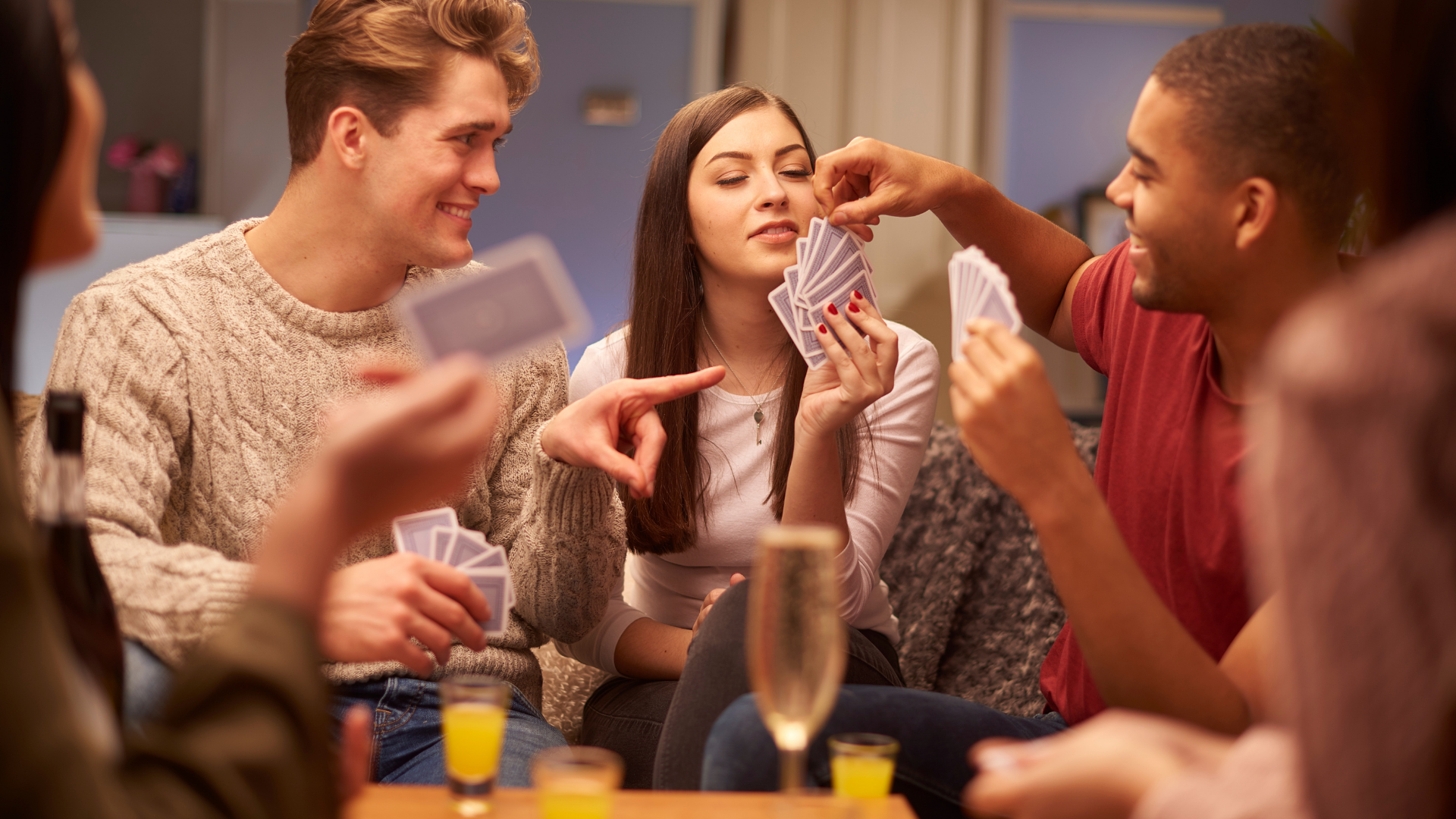 students laughing playing cards at table