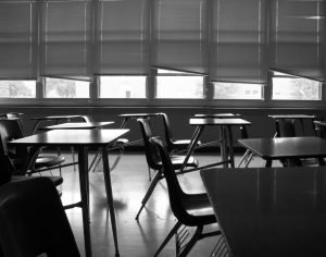 A black and white photograph of an empty classroom.
