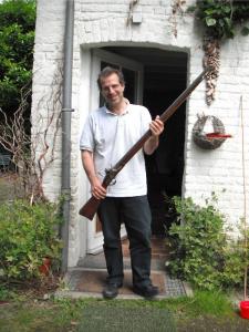 A short Italian man holding an extremely long gun.