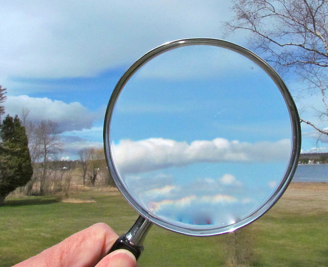 Magnifying glass held up to a countryside landscape