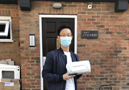 A UKC Chinese Society student wearing a mask and holding a care package