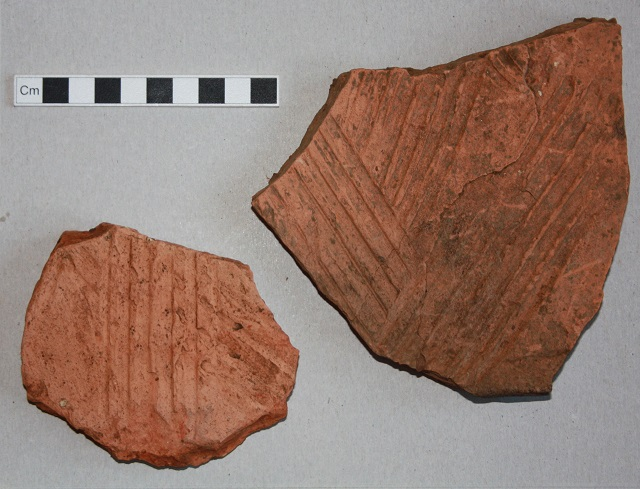 Fragments of box flue tiles; the larger piece came from Feature 2020, and shows sooting over its interior surface indicating use. Here we show the outer surface.