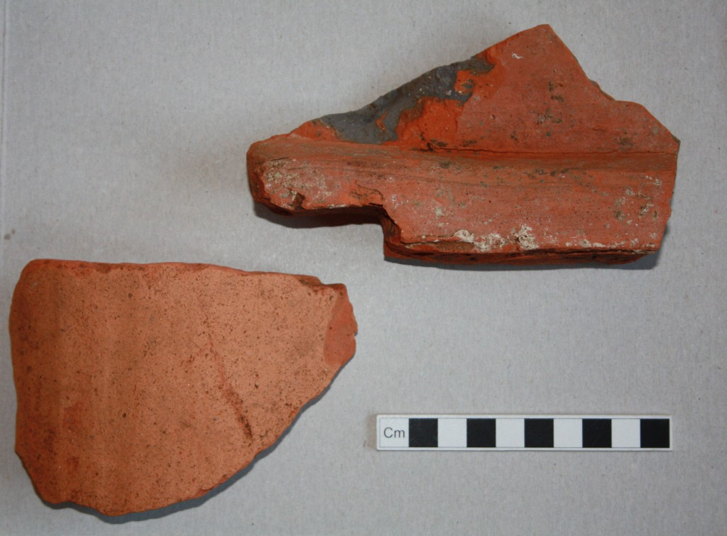 Two fragments from Roman roof tiles. The fragment on the right comes from the broad flat type (known as tegulae) which would have covered most of the roof area. This example shows traces of mortar for attachment of the arched tile type (known as imbrices) which sealed the joins between tegulae. Presumably our mortared example here had been used for roofing at our site.