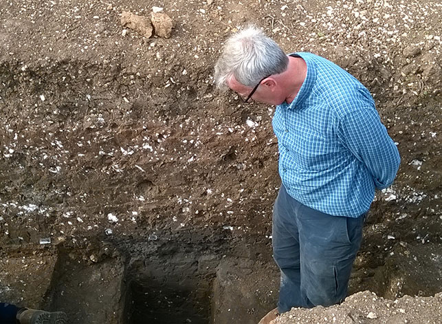 Graham contemplating how far off from reaching the bottom of feature 2020 we are, in our deepest excavated section.