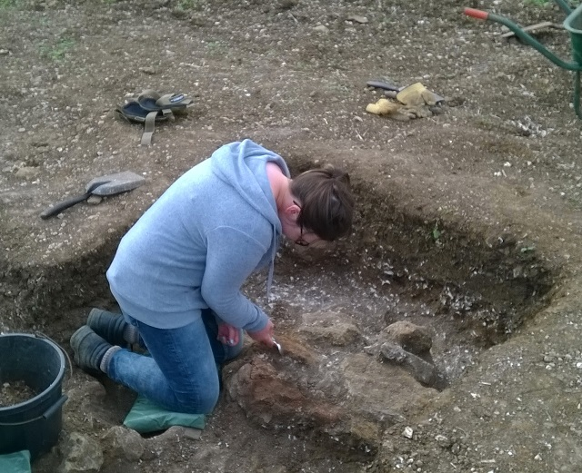 Toni carefully cleaning our newly discovered post pad within the Roman building, for a detailed photograph