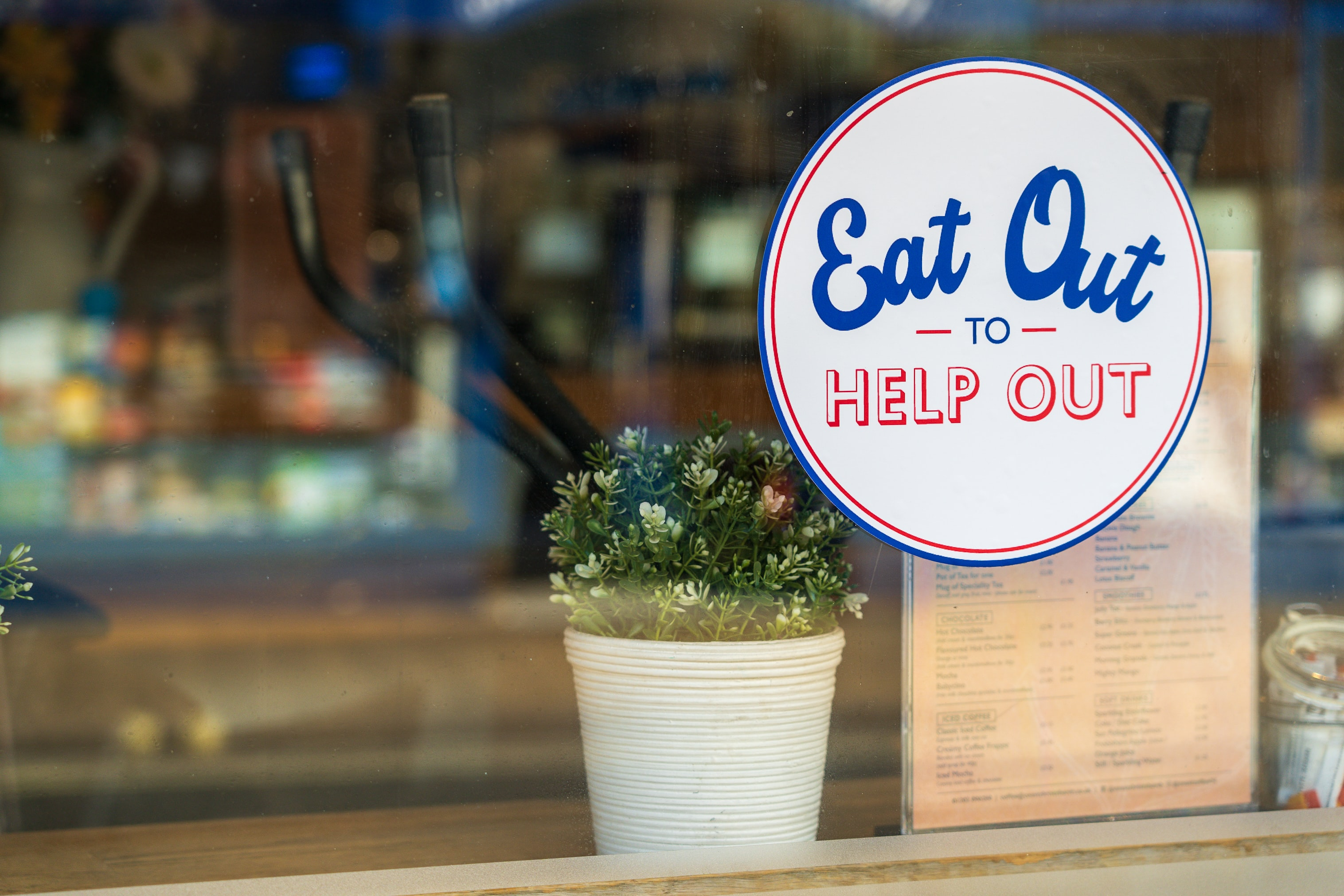 Eat Out to Help Out logo in a window next to a plant