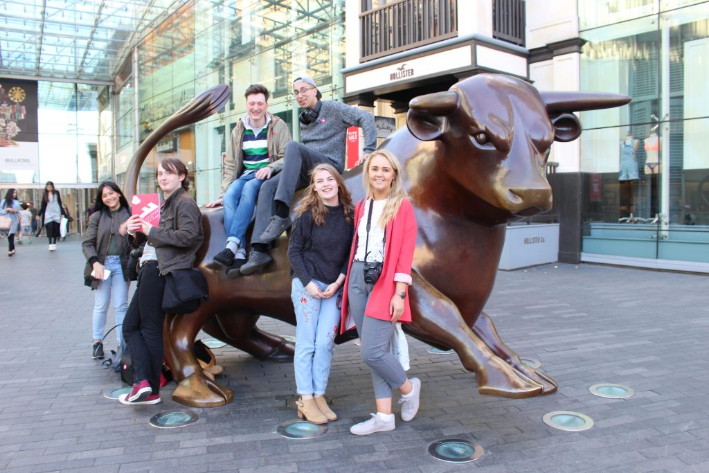6 students sitting on and standing in front of Bull sculpture