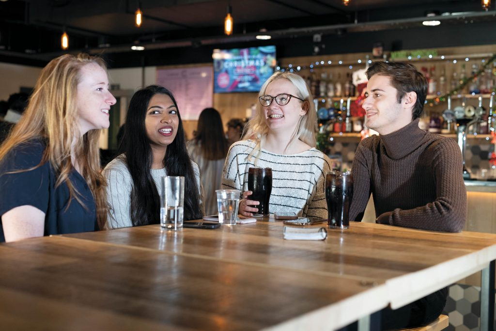 4 students sat around a bar table with drinks