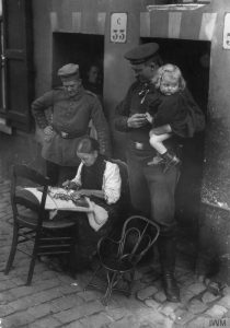 © IWM Q87606. German soldiers watching a female lacemaker at work in German occupied Belgium