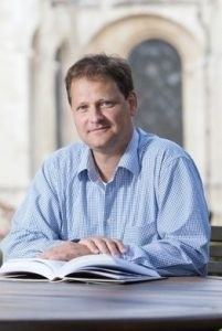 Professor Ulf Schmidt with a book sitting at a table in front of Canterbury Cathedral.