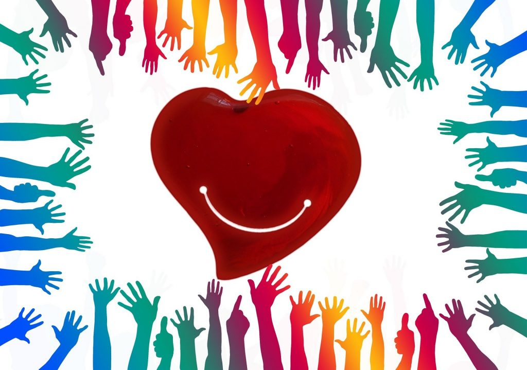 Smiling read heart on white background. Hand reach out to the heart from all sides. Hands are coloured in various shades of green, blue, yellow, orange, pink and purple.