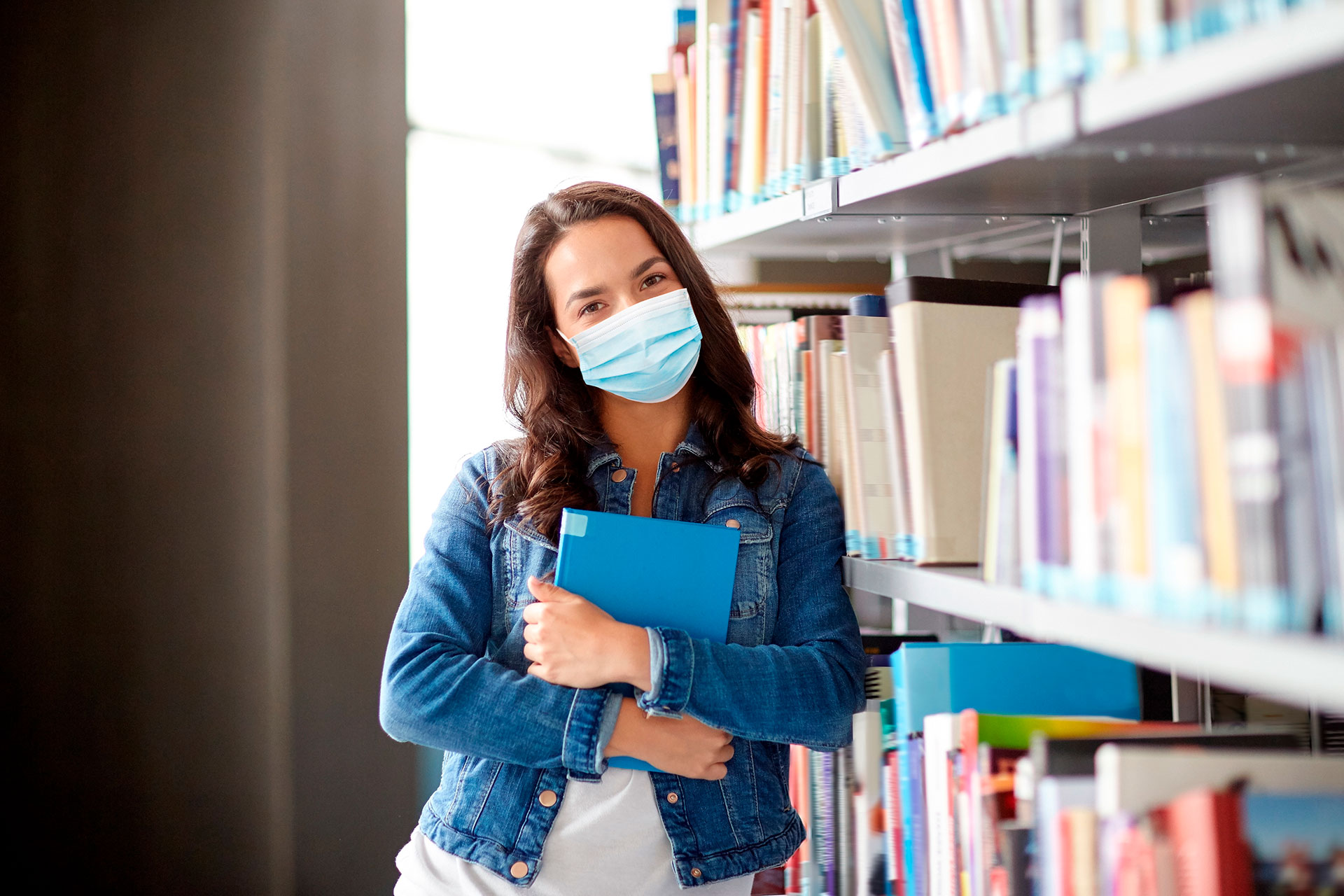 Mask wearing female student standing next to bookshelves and holding book