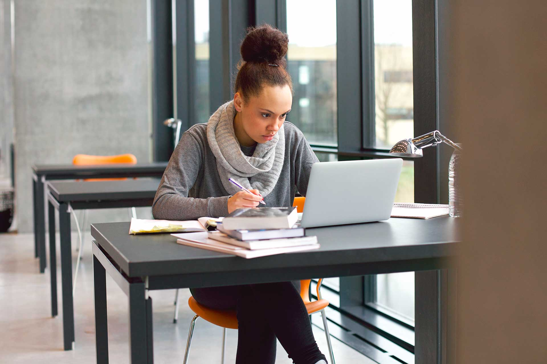 Female student taking notes at study desk with laptop