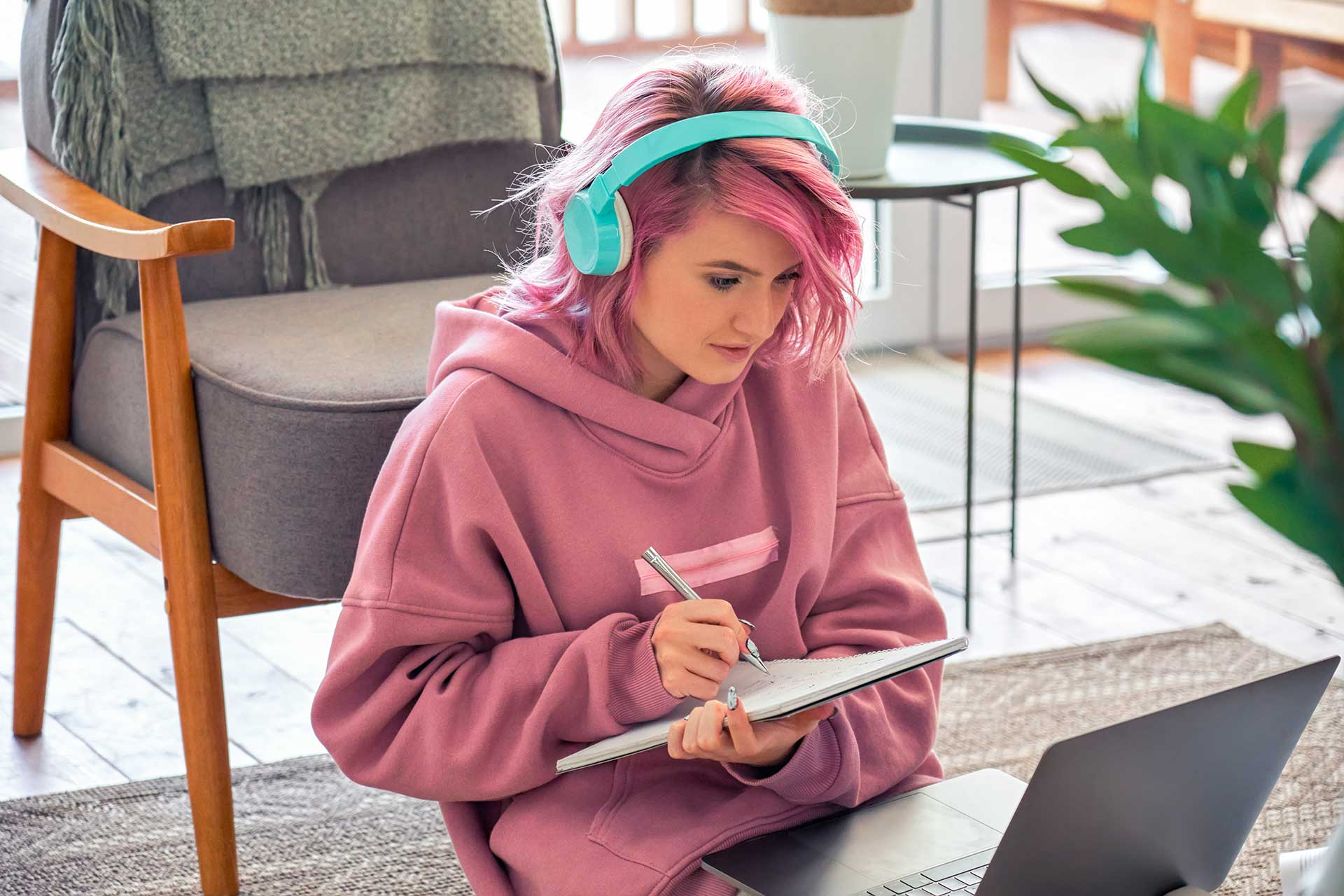 Female student with headphones taking notes while looking at laptop