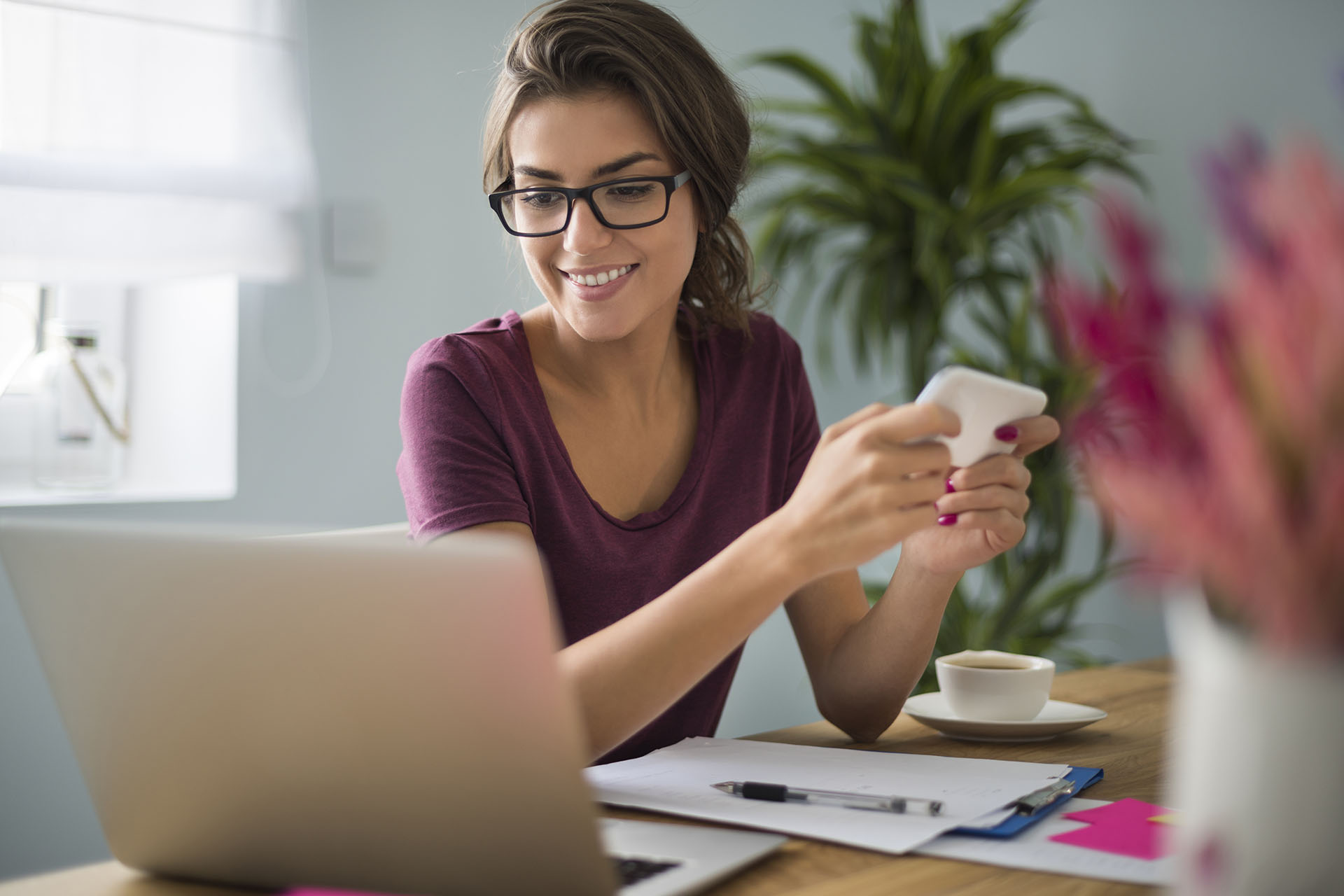 Woman holding mobile phone and looking at laptop