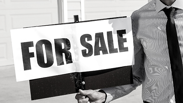 Handheld 'For Sale' sign, black and white