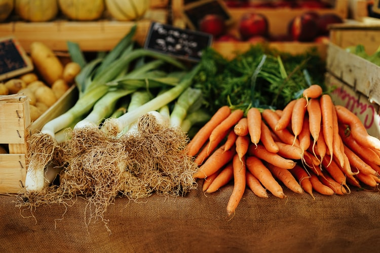 Wooden table with fresh vegetables and two piles of leeks and orange carrots