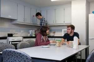 An image of students relaxing in a kitchen