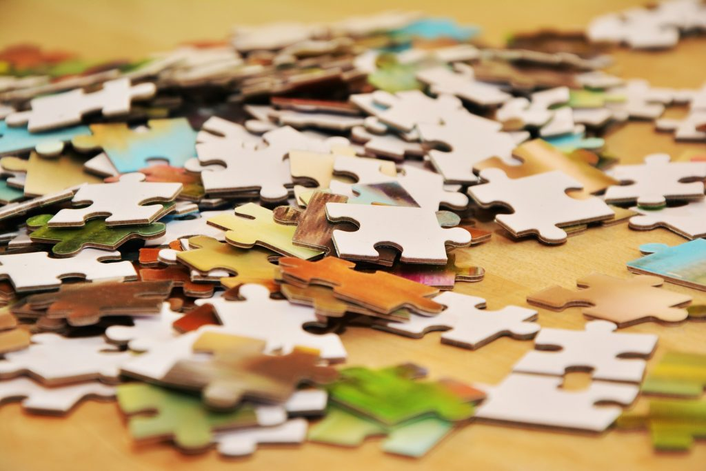 Pieces of a puzzle strewn across a table