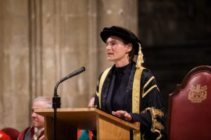 Professor Karen Cox in ceremonial attire, standing behind a lecturn at the Congregations event