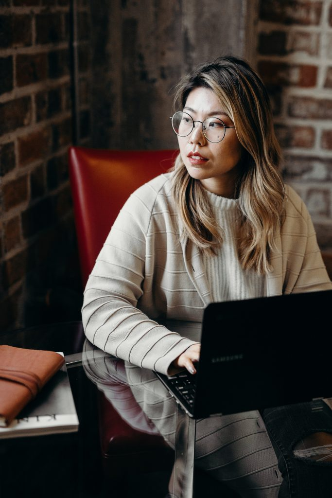 Woman sitting in front of laptop looking thoughtful