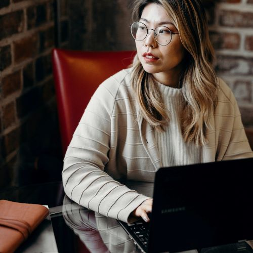 Woman with laptop staring into space looking thoughtful