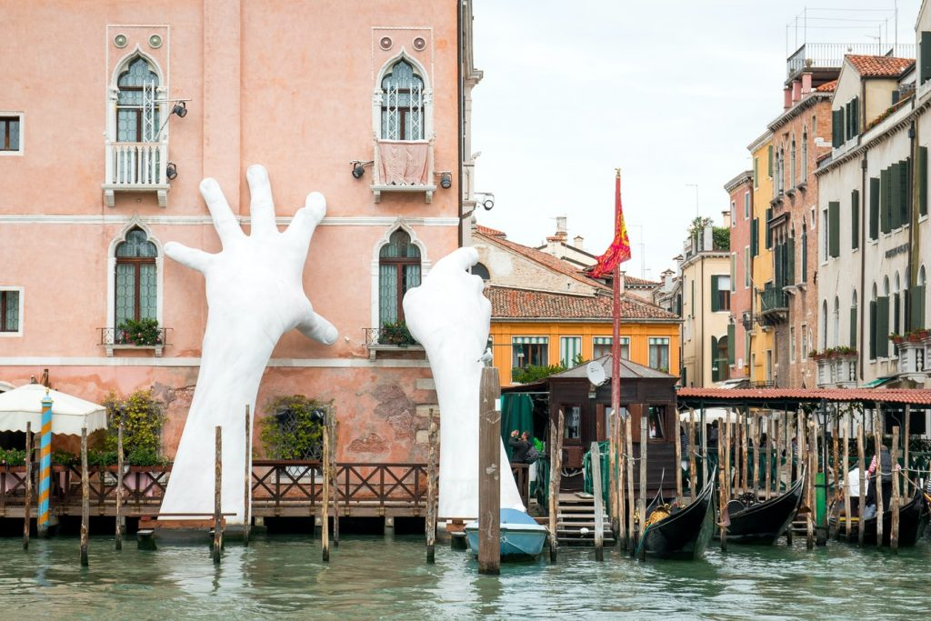 Large white sculpted hands, raising out of canal, supporting a tall building.