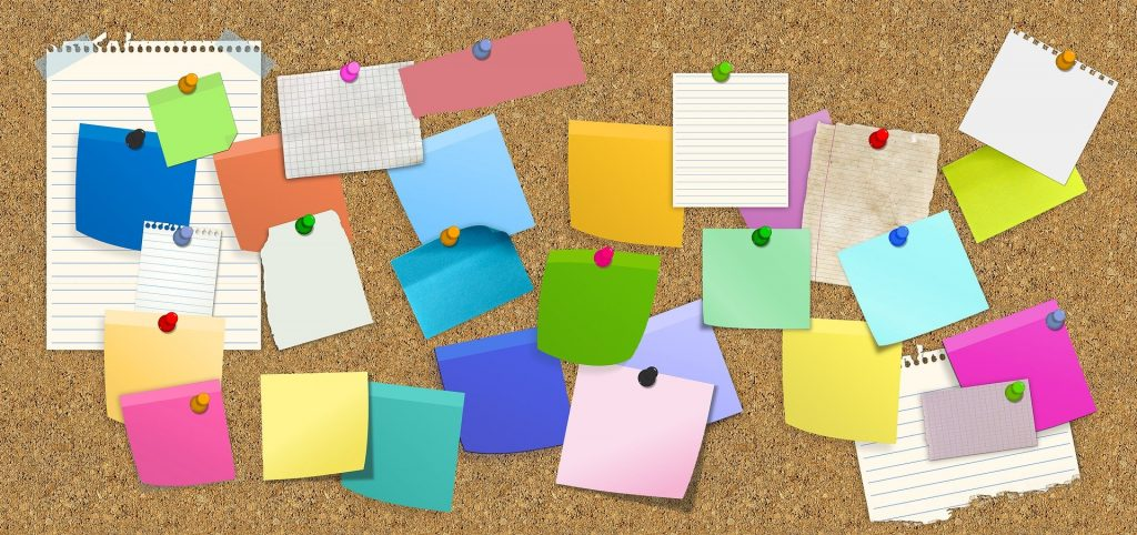 Post it notes scattered on a corkboard