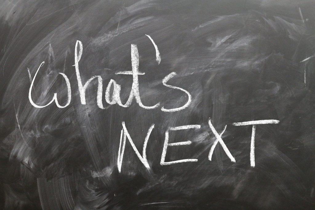 Blackboard with handwritten chalk text: what's NEXT?