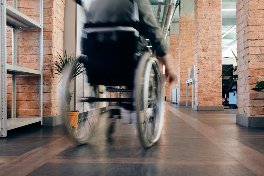 view of wheelchair from rear, floor level., moving through a tile floor corridor with red brick columns.
