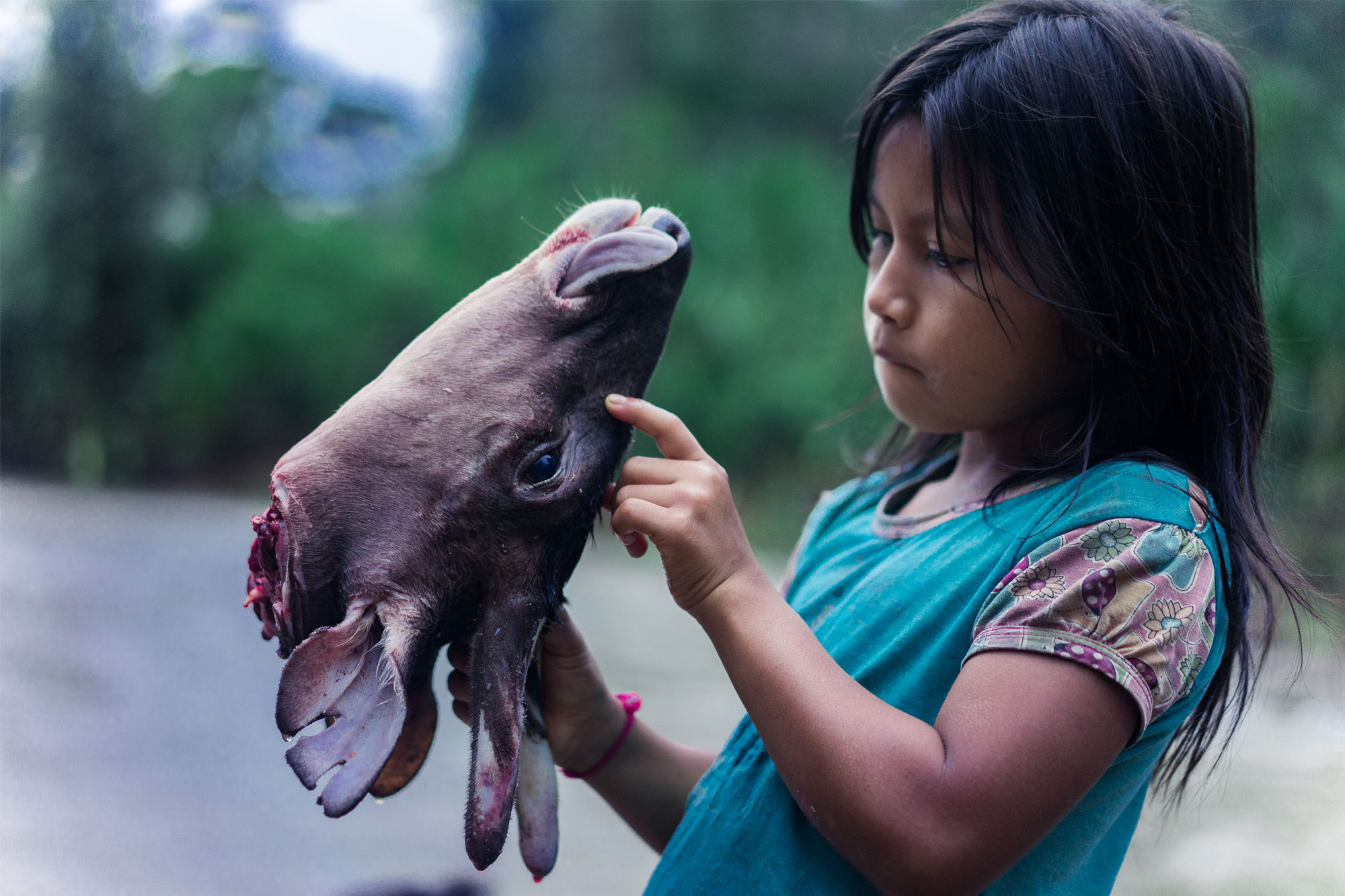 Girl holding a severed deer's head