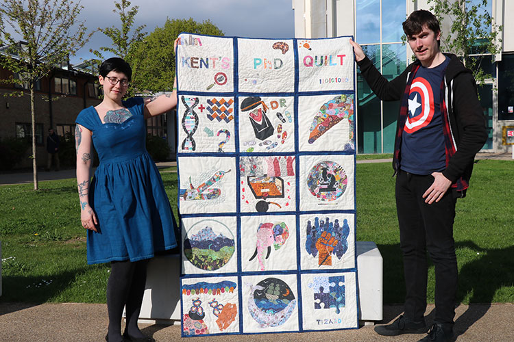 Laura Thomas-Walters holding the Kent PhD quilt with fellow DICE student Steven Allain