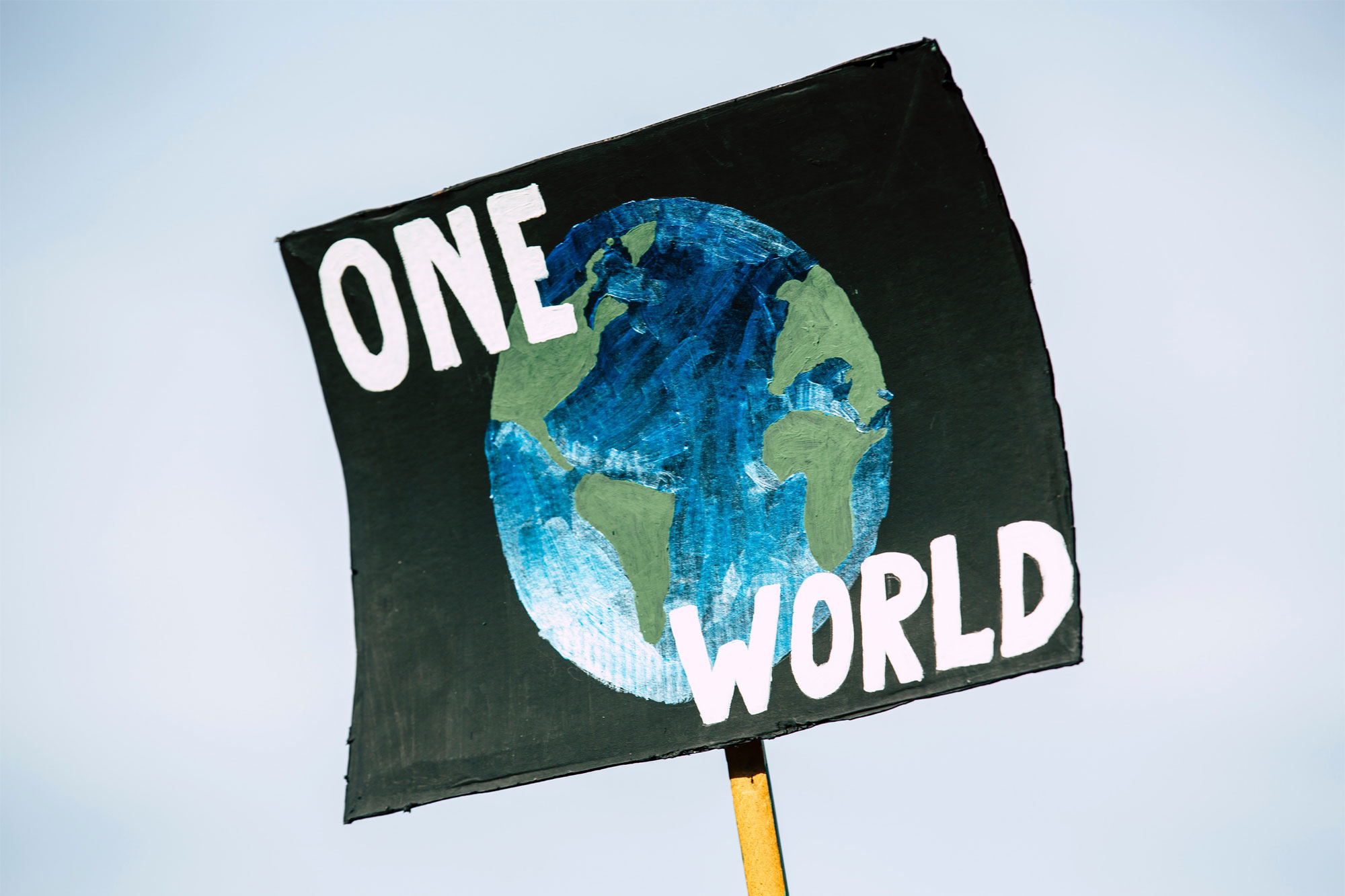 Placard held aloft: 'One World'