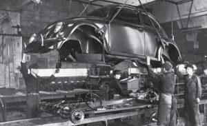 Workmen assembling a Volkswagen Beetle.