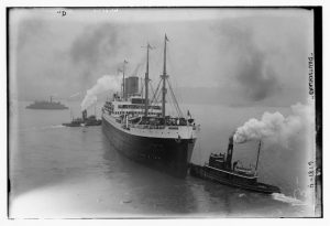 A picture of the ship SS Deutschland and two tugboats with smoke and steam emerging from their funnels.