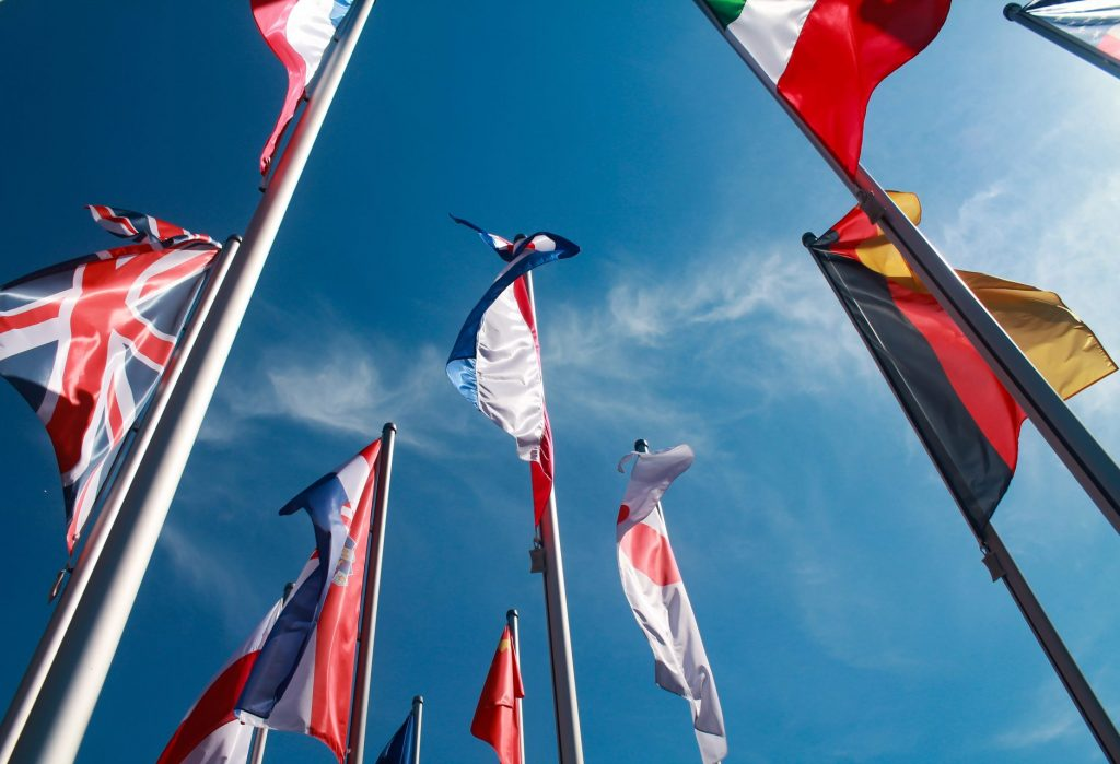A ground view of flags of many different countries against a blue sky