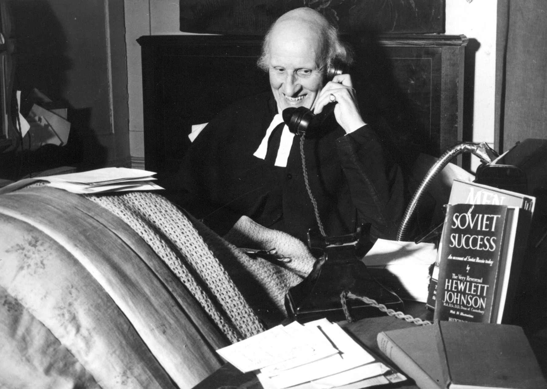 Dean Hewlett Johnson smiling whilst holding a telephone; one of his published books is beside him.