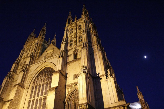 A half moon rising behind Canterbury Cathedral at night. Kent.