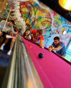 winning photo of pink pool table with friends and colourful wall in background