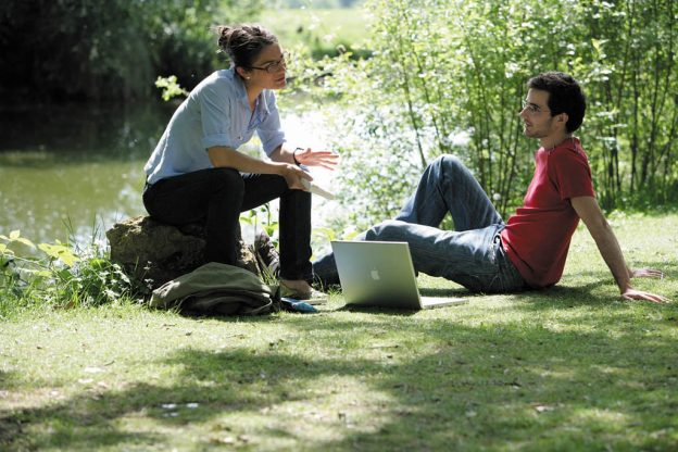 two people sitting by a pond on campus