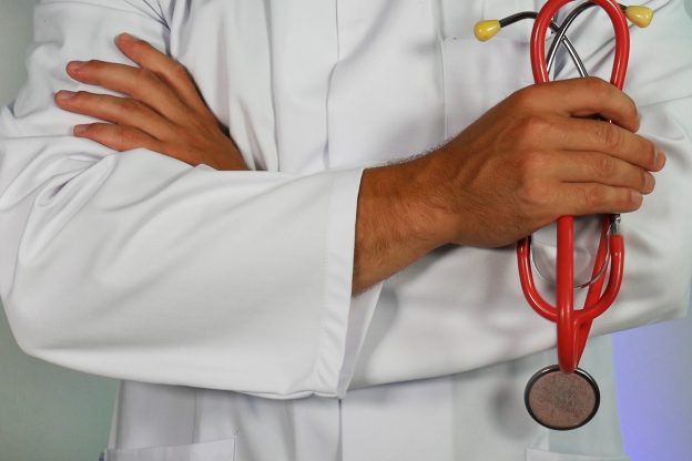 close up of doctors arms holding stethoscope