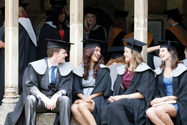 group of students in graduation gear sitting smiling at each other