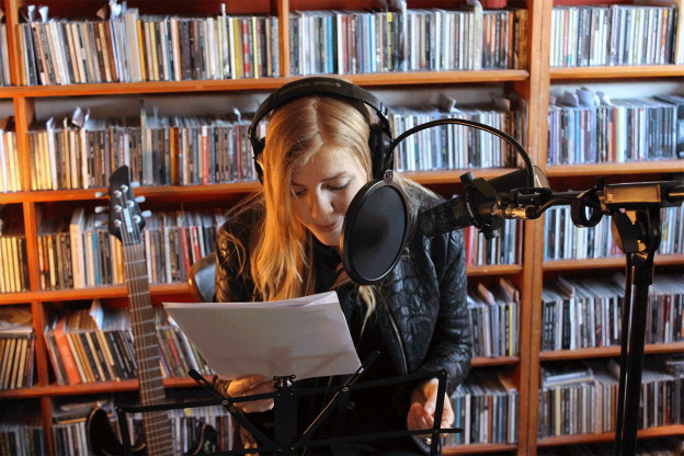 women with headphones and mic recording podcas infront of shelves of books
