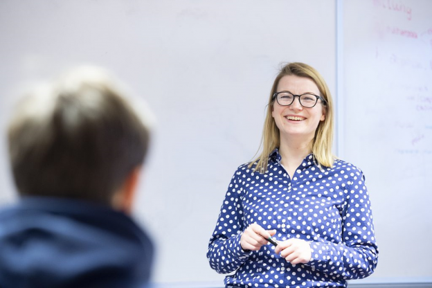 Lecturer Laura Bailey smiling standing infront of whiteboard