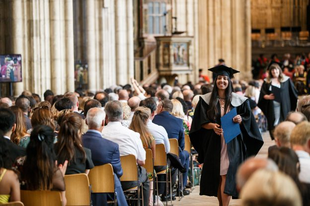 Student walking in Canterbury Cathedral after collecting their degree