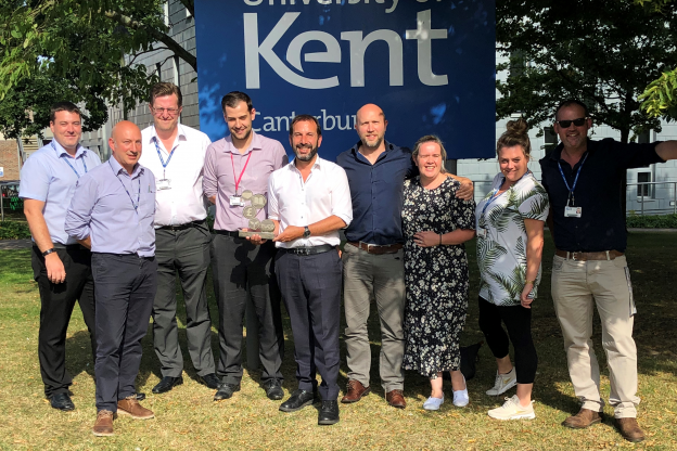 Staff from Kent Hospitality holding their TUCO award infront of the University of Kent sign