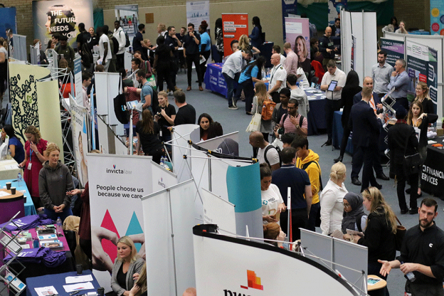 Careers fair stands with lots of students talking to employers