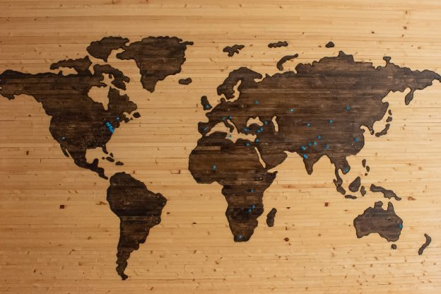 Wooden map of the world with pins