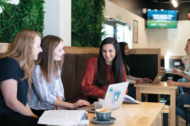 Three girls sitting at desk looking at laptop