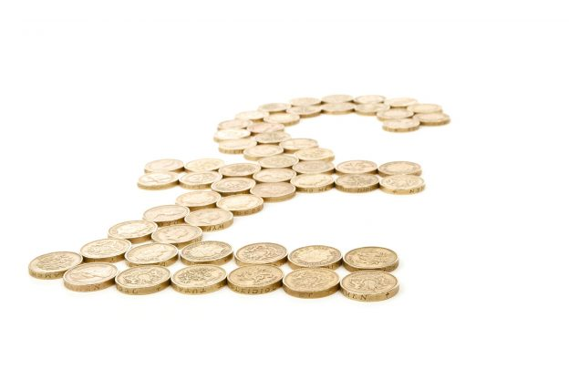 Pound coins laid out in shape of pound sign